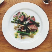 Rack of lamb with peas, broad beans, artichoke purée and a potato cake wrapped in pancetta